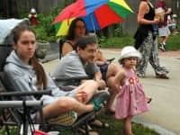 At right, Evangeline Makin, 2, with her parents, Malcolm and Melanie, and, though not visible here, her brother, Isaac,  3 months, watch the 2014 Gaspee Days Parade.
