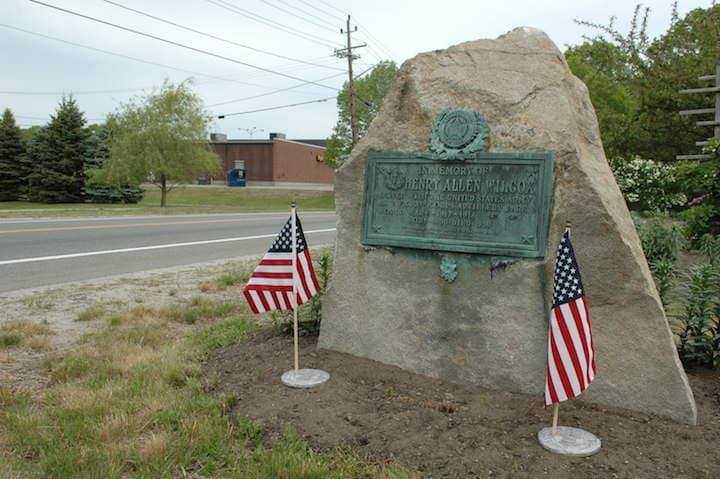 A small memorial adorned with flags alongside Warwick Avenue near Bishop Hendricken High School.