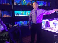 Something Fishy owner Kurt Harrington explains the in-aquarium reproduction of corals to Congressman Jim Langevin May 8.