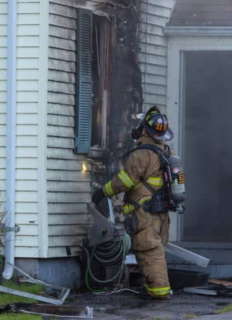 [Brian Calci] A Warwick Firefighter inspects the damage done by a fire at 57 Puritan Drive Wednesday evening.