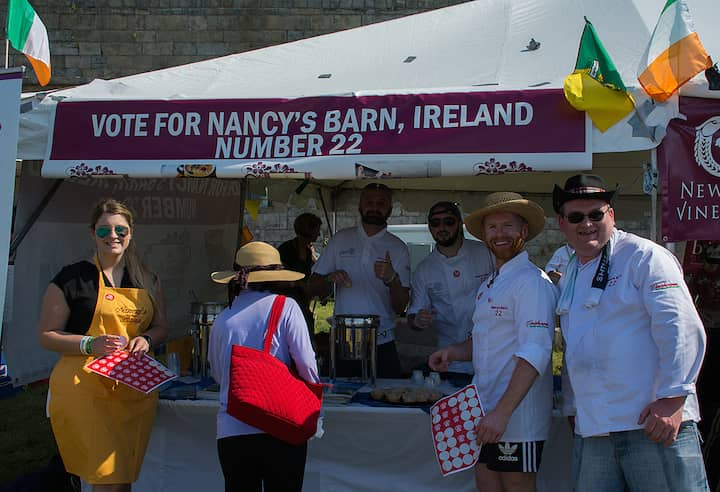 [CREDIT: Mary Carlos] Nancy's Barn, hailing from Ballyliffin Ireland, serves up their chowder at the Great Chowder Cook-Off at Fort Adams, Newport. At far right, in straw hat, Gavin McNaulty, owner, charms the crowd. With him are Ronan Gildea, Bernard Harkin and Kieran Duey.