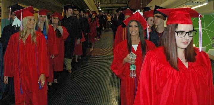 {CREDIT: Rob Borkowski] Toll Gate High's Class of 2019 graduates march toward the CCRI field house for graduation.