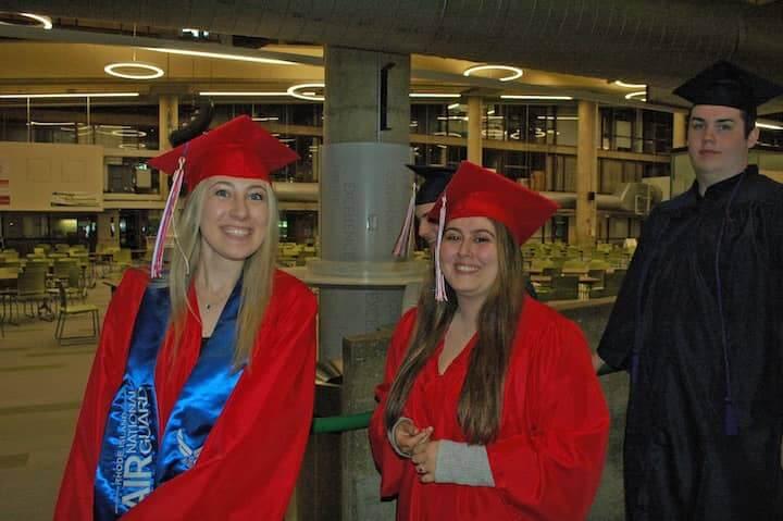 {CREDIT: Rob Borkowski] Savannah Cozza pauses for a smile as she heads toward the CCRI field house for graduation.