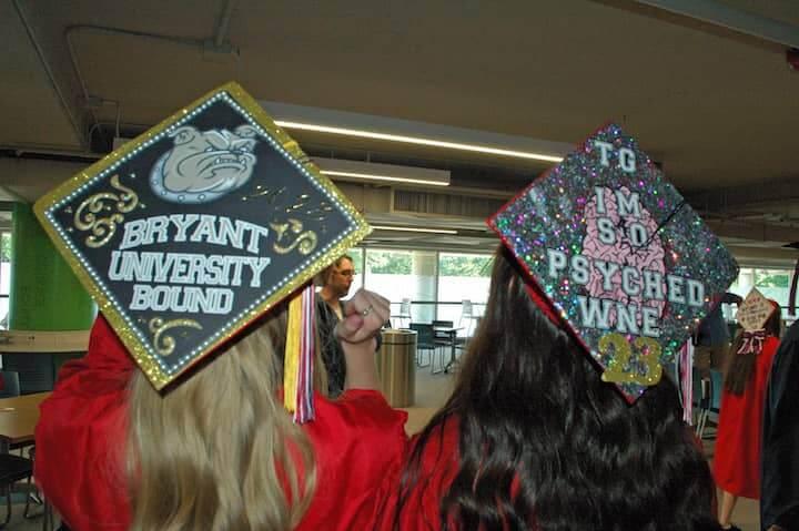 {CREDIT: Rob Borkowski] Brianna Jankowski and Madison Jackson show off their cap decorations on their way to graduation at CCRI June 6, 2019.