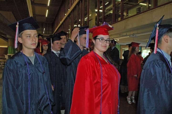 {CREDIT: Rob Borkowski] Michael Bastien, Jordan Beaumier, and Jazmine Barratt march toward the CCRI field house for graduation.